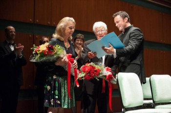 "Helmuth and Martina Rilling, with Matthew Halls, looking at the score of James MacMillan's ""Allelulia"" at its July 6 world premiere."