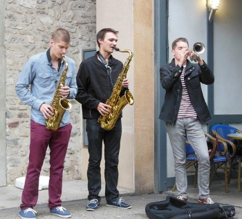 Busking musicians Jared Yakel and Joshua Hettewer (sax) and Tony Glausi (trumpet) in Vienne, France. Photo: Lance Miller.
