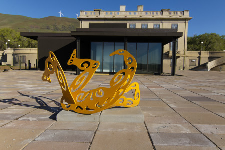 "Plaza, Mary and Bruce Stevenson Wing, with original museum building behind. On the hills are some of the windmills that help support Maryhill financially. Foreground: Alisa Looney (Portland, Ore.), ""Roll & Play,"" 2007, powder-coated and flame cut mild steel, 36"" x 75"" x 48"". Gift of the North Star Foundation, 2008.06.001. Photography Scott Thompson"