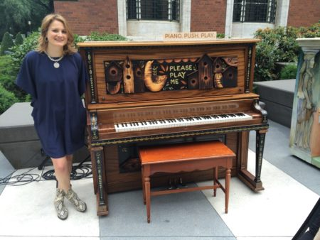 Pianopushplay founder Megan McGeorge poses next to a piano she donated to the cause at this summer's opening event.