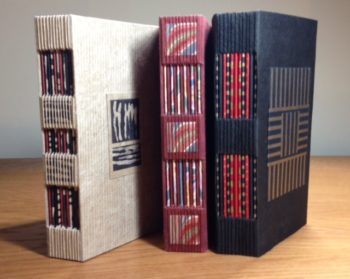 Three of the books Connie Stricks will have in the show include open spines that allow colorful folios to peek through.