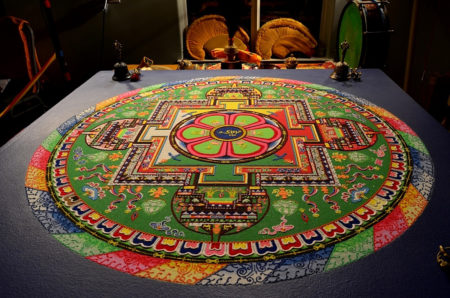 "The Manjushri Sand Mandala is one of the many designs the monks have spent years learning to make. In the background are the formal head-gear the monks wore for ceremonies and rituals, as well as the drum and musical instruments used in ceremonies. Bells and ""dorjes"" or ""vajras"" (thunderbolts) on the corners of the table carry shapes and designs with symbolic meaning. Photo by: Tripp Mikich"