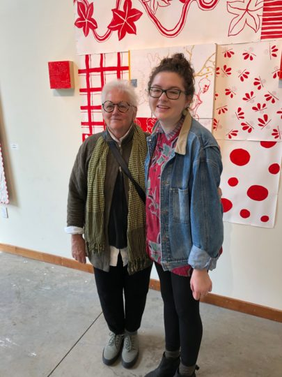 """Salem artist Bonnie Hull (left) and Sarah Rosella Cuevas, a 2019 George Fox University graduate in arts administration, take a break during  installation of Hull's """"Little Me"""" exhibit at the university, which was curated by Cuevas.  Photo courtesy: Bonnie Hull"""