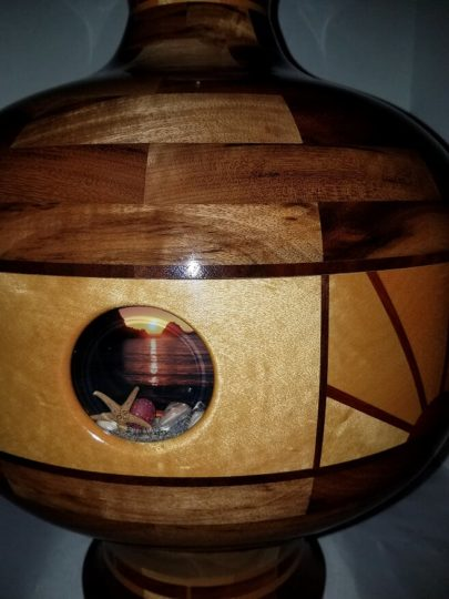 """Mike Brown's segmented wood vase, """"Oregon Coast Tidepools and Sunset,"""" includes beach sunsets visible through portholes."""