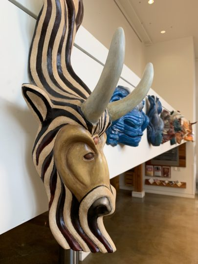 """Capricorn, the Goat,"" from Kike Mayer's ""Zodiac"" mask series, greets visitors from above the lobby the Chehalem Cultural Center in Newberg. Photo by: David Bates"