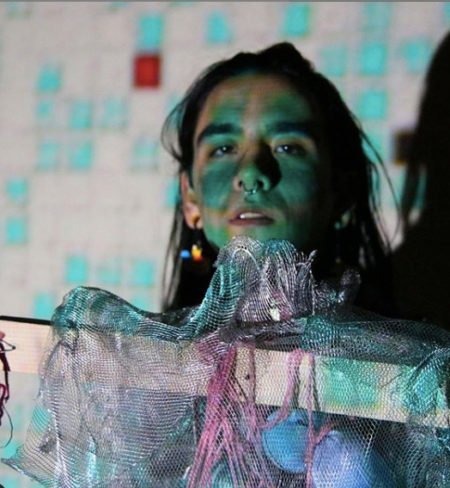 Photo of artist during performance, looking at viewer from behind wood decorated with  scrap of silver metallic netting and pink yarn, with turquoise squares projected over all.