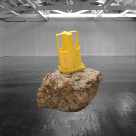Photo of an empty room with a yellow plastic item that might be an industrial component or part of a toy sitting atop a large beige rock.