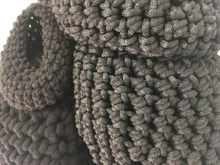 Close up image of rounded sculptural shapes made from crocheted black rope with several different textures.