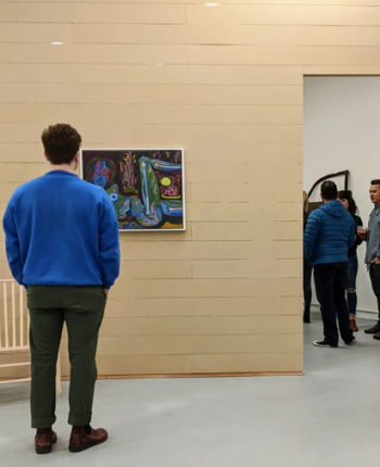 View of Ditch Projects gallery, with people talking in the background while in the foreground a man in blue shirt stands in front of beige wall looking at a painting of a green and blue alien woman.