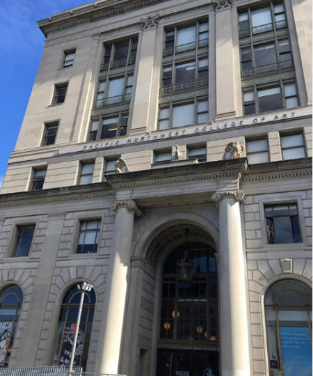 Exterior of historic PNCA building in downtown Portland, features arched windows, small gargoyles above main entrance, and neoclassical columns and detailing.